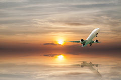 Airplane flying tropical sea at sunset time with reflection Stock Image