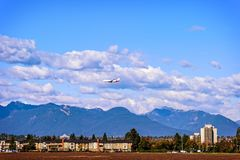 Airplane flying under the clouds over the buildings. And mountains in a blue sky royalty free stock photography