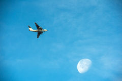 Airplane flying under the moon Stock Images