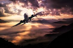 Airplane Flying Under White Clouds during Night Time Stock Image