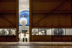 Airplane in front of half opened door to hangar. Blue airplane in front of half opened door to hangar Royalty Free Stock Image