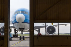 Airplane in front of hangar. Airplane in front of half opened door to hangar stock photo