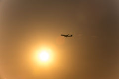 Airplane in front of a hot evening sun. An airplane in front of a hot evening sun Stock Image