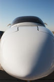 Airplane front part. Closeup of airplane nose with blurred pilot cabin against blue sky Stock Photos
