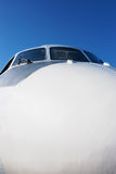 Airplane front part. Closeup of airplane nose with pilot cabin against blue sky, selective focus Royalty Free Stock Images