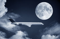 Airplane and a full moon Stock Photography