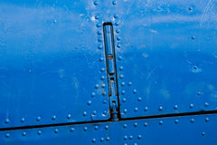 Airplane fuselage area with a lock. Closeup view of a fuselage area of a vintage aircraft. The area is covered with rivets and painted blue. You can see also a Stock Photography