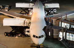 Airplane at gate during delivery catering service. Food, drink, goods at night royalty free stock photos