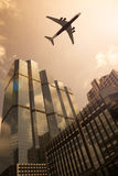 Airplane in a golden sky. With modern buildings royalty free stock photo