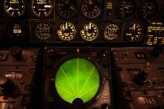 Airplane green glowing radar with aircraft gauges, switches, and Royalty Free Stock Image