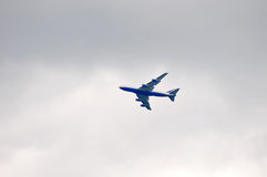 Airplane in grey skies Stock Images
