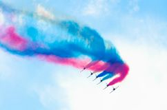 Airplane group fighter against the background of color smoke. Royalty Free Stock Image