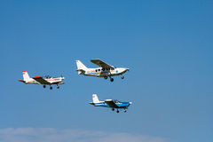 Airplane. A group of small propeller airplanes in red, blue and white on a flight show flying in the air Stock Photography