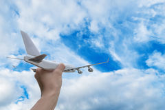 Airplane on hand in blue sky Stock Photography