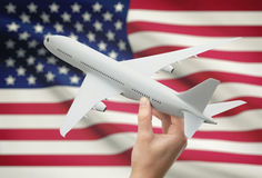 Airplane in hand with flag on background - United States Royalty Free Stock Photo