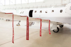 Airplane in Hangar with remove before flight Labels in red. Warning safety Royalty Free Stock Photography
