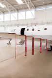 Airplane in Hangar with remove before flight Labels in red. Warning safety Royalty Free Stock Photos