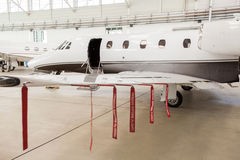 Airplane in Hangar with remove before flight Labels in red. Warning safety Stock Image