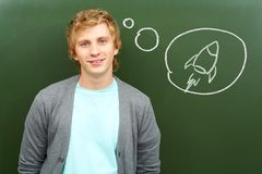 Airplane hobby. Portrait of smart lad by the blackboard thinking of flying on airplane Royalty Free Stock Photo