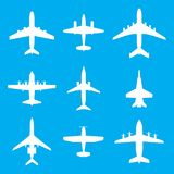 Airplane icons set isolated on blue background. Vector white silhouettes of passenger aircraft, fighter plane and screw. Airplane icons set isolated on blue Stock Photography