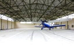Airplane. Inside a big hangar, blue plane Royalty Free Stock Photo