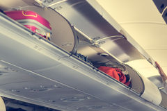 Airplane interior with overhead luggage compartment. Doors opened before take-off Stock Photo