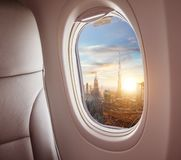 Airplane interior with window view of Dubai city. UAE. Concept of travel and air transportation stock images