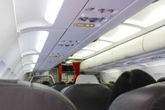 Airplane interiors. Interior of airplane with passengers.No smoking sign and seat belt sign on the airplane royalty free stock images