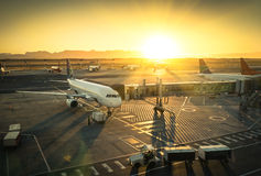 Airplane at international airport terminal gate. Airplane at the terminal gate ready for takeoff - Modern international airport during sunset - Concept of Royalty Free Stock Image