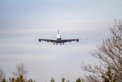 Airplane ist landing. Front view of a jet airplane approaching an airport for landing Stock Photo
