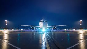 Airplane jet rolls in parking postion on airport at night stock footage