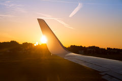 Airplane jet wing at sunset with golden sunlight Royalty Free Stock Photos