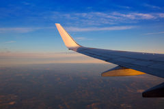 Airplane jet wing at sunset with golden sunlight Royalty Free Stock Image