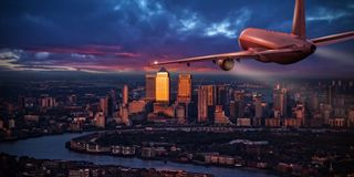 Airplane jetliner flying above business district of London. Commercial airplane jetliner flying above business district of London. Travel and business Stock Images