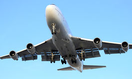 Airplane landing. Large airplane landing on a clear blue sky Stock Photos