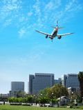 Airplane landing. Brilliant blue sky, park and cityscape, being, commuter, skyline royalty free stock image