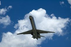 Airplane Landing. An airplane is landing with a blue sky against a white puffy cloud Stock Photos