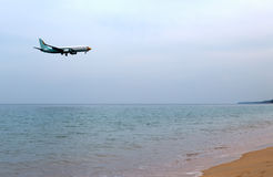 Airplane landing above beautiful beach Royalty Free Stock Image