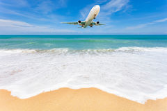 Airplane landing above beautiful beach and sea background. Stock Photo