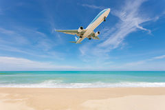 Airplane landing above beautiful beach and sea background. Royalty Free Stock Photo