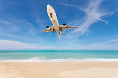 Airplane landing above beautiful beach and sea background. Royalty Free Stock Photos