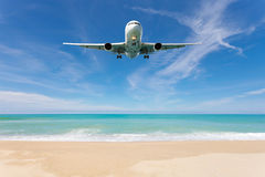 Airplane landing above beautiful beach and sea background. Royalty Free Stock Images