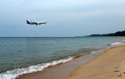 Airplane landing above beautiful beach and sea background Royalty Free Stock Photos