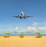 Airplane landing above beautiful beach Stock Image