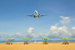 Airplane landing above beautiful beach Stock Photography
