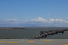 Airplane landing on the airport. With blue sky, clouds, and San Mateo Bridge underneath Royalty Free Stock Image