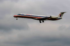 Airplane landing (American Aitlines ). AA American Airlines landing, photographed in aviation observatory. plane and clouds Stock Photo