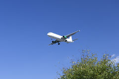 Airplane landing in Bremen. White Airplane landing with blue sky and tree Stock Photo