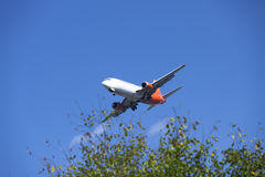 Airplane landing in Bremen. White and orange Airplane landing with blue sky and tree Royalty Free Stock Photo