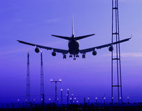 Airplane landing at dusk Stock Photos